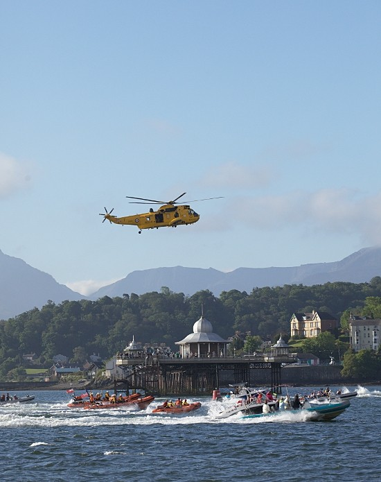 Flotilla of RAF rescue helicopter and boats accompany the Olympic torch down the Menai Strait