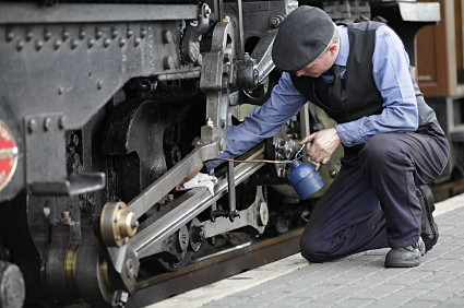 Locomotive driver oiling bearings before next journey