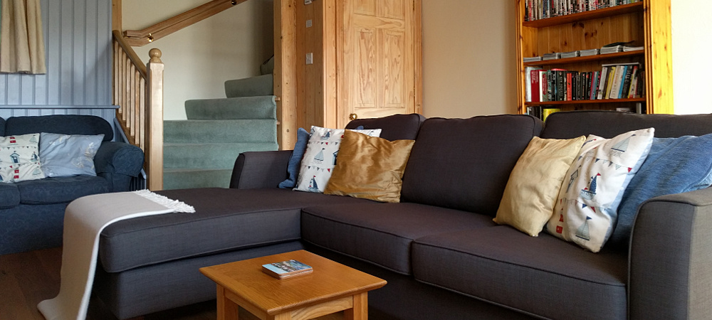 cottage living room shows comfy settee, bookcase and staircase behind