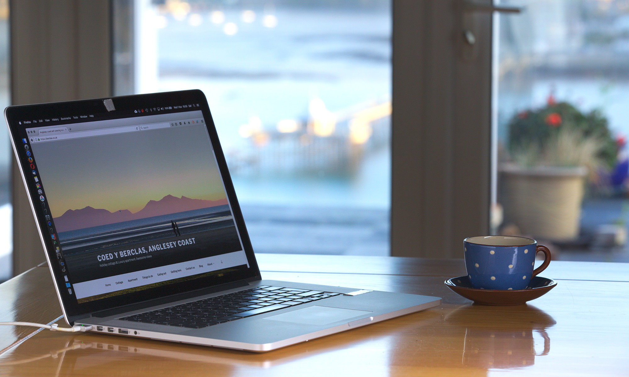 Image of a laptop with Coed y Berclas logo on screen for the contact us page.