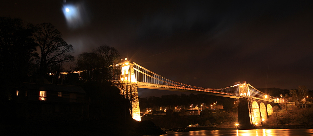The Telford Suspension Bridge at Menai Bridge under a misty moon